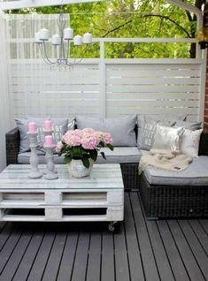 idee deco terrasse, meubles en palettes peintes en blanc, luminaire avec des ampoules blanches, table palettes blanc a roulettes, canapé rotin d'angle, sol recouvert d'éléments en bois noir