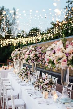 Wedding lighting for elegant outdoor spring wedding reception party using CV Linens polyester tablecloths and artificial flowers for centerpieces. Beautiful outdoor wedding party decorations for guest tables using string lights and tall flower centerpieces. #weddingtabledecorations #weddingtablecenterpieces #springweddingcolors #springwedding #springweddingreception Summer Wedding Centerpieces, Wedding Table Decorations, Flower Centerpieces, Backyard Wedding Lighting, Outdoor Wedding Reception, Reception Party, Rustic Wedding, Summer Wedding Colors, Spring Wedding
