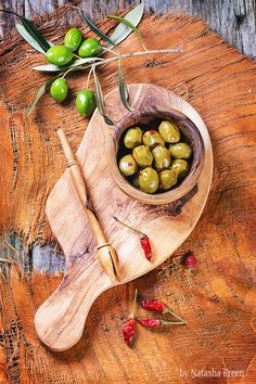Green Olives - Green olives in olive wood bowl with chili pepper and olive's branch served on cutting board over wooden table. Top view.