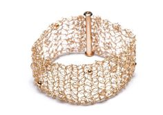 Handmade gold filled knitted mesh cuff with small interwoven gold beads and champagne coloured swarovski stones.  http://www.pennylevi.com/
