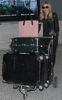 Travelling in style: Accessorising with a pair of sassy sunglasses, Olivia made her way through the terminal with three suitcases and a stylish oversized handbag