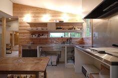 森を望む家のキッチンはステンレス天板のオーダーキッチン . このキッチンは勾配天井でトップライトからやさしい光が入り込みます 昼間は電気がついているようですが北側を向いているトップライトなので柔らかな光が差し込みます . ステンレスでハードな雰囲気の天板のキッチンではありますがステンレスの天板に壁の羽目板や森がうつり込むのであまりハードに見えないステンレス天板キッチンです . 天板の高さは90センチ 奥様の思いとしてはご主人の身長に合わせて少し高めのキッチンにシンプルな深めのステンレスシンクを製作して家事の分担をしやすくしてあります