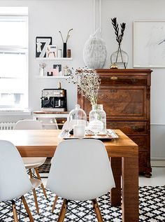 Effortlessly mixing modern and vintage in the dining room, by sticking to a monochrome and warm wood palette.
