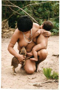 Índia amamenta filhote de porco do mato (Prêmio Internacional Rei da Espanha)  Foto flagrou índia da tribo Guajás, no Maranhão, amamentando filhote criado na aldeia.    (Foto: Pisco Del Gaiso/Folhapress)