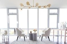 Gray glass and brass modular chandelier illuminates a pair of white linen wingback chairs facing each other across from a pair of gray wood tree trunk tables atop a gray wool rug placed in front of floor to ceiling windows.