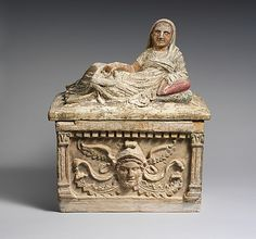 Terracotta cinerary urn Hellenistic,2nd century B.C. The container depicts a fantastic head with bovine ears and wearing a Phrygian cap with wings. This soft, cloth cap was worn by the people of ancient Phrygia (modern central Turkey).
