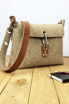 Womans handbag which is handmade from 3 mm industrial wool felt, and is assembled using pop rivets. The strap is made from 100% vegetable tanned