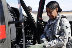 Army 1st Lt. Demetria N. Elosiebo puts on her gear before entering the cockpit of a UH-60 Black Hawk helicopter at Davison Army Airfield, Va., March 15, 2014. Elosiebo is a platoon leader assigned to Company D, Air Ambulance, 1st Battalion, 224th Aviation Regiment.  Elosiebo is the first female African-American rotary wing pilot in the D.C. Army National Guard. Army National Guard photo by Staff Sgt. Mitch Miller