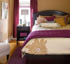 Plum + Sand:   In this snug bedroom, neutral basics -- a dark wood bed frame and nightstand, tan walls, ivory chair, and duvet cover -- cozy up with plum accents in the rug, blanket, pillow, curtains, and art. Purple can represent either cool or warm parts of the color spectrum, depending on the hue. Look for shades of purple that have a slightly red hue to pull out the warm tones in a room.