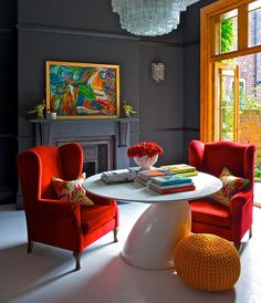 Eclectic design with traditional trim, high gloss modern white table, dark graphite gray walls, and saturated red wings chairs.