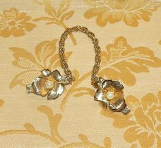 This is a beautiful vintage gold tone Sweater Guard with a floral design and a real pearl center. The flower is brushed gold with fine details https://www.etsy.com/listing/223323800/sweater-gurad-clips-vintage-1958-sweater