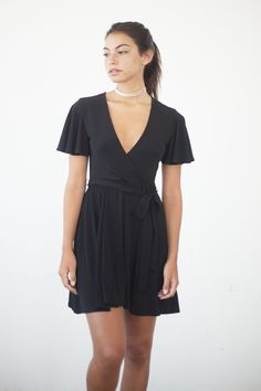 """- Details - Size - Shipping - • 95% Polyester 51% Spandex • Soft flutter sleeve wrap dress • Hand Wash • Line dry • Made in the U.S.A • Measured from small • Length 32"""" • Chest 13"""" • Waist adjustable"""""""