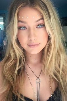 Hadid nailed the boho goddess look with soft waves, glowing skin, face jewels and a Guess body chain. @gigihadid - HarpersBAZAAR.com