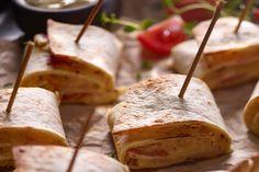 Przepis na łatwą i szybką przystawkę na ciepło – zapiekane roladki z tortilli z serem, szynką i salami.