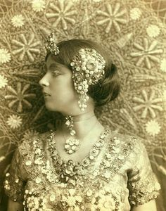 the tiny jewel-encrusted tiara, necklaces and dress are still worn today but the side headpiece, above the ears but not earrings is sensationally opulent.  and the textured background is phenomenal.  1910 1920 flapper fashion