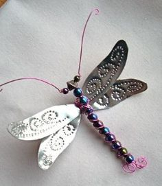 Punched tin, beads, and wiring make this beautiful dragonfly ornament. can be made from pop cans also ~ could be a lapel pin as well. Tin Can Art, Soda Can Art, Tin Art, Wire Crafts, Metal Crafts, Jewelry Crafts, Jewelry Ideas, Soda Can Crafts, Fun Crafts
