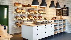 Una panadería con estantes blancos y muebles en blanco/abedul macizo