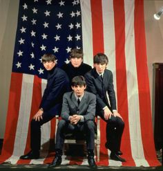 The Beatles pose with an American flag in a Paris photo studio before their first visit to the United States, in January 1964.