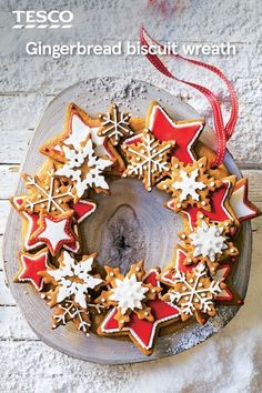 Turn delicious Christmas gingerbread biscuits into a gorgeous showstopper with this gingerbread wreath recipe. Easy to make at home, this Christmas bake with its crunchy, spiced biscuit stars and snowflakes makes a stunning edible centrepiece. | Tesco
