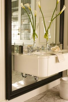 Photo Gallery: Bathroom Makeovers | House & Home ::A mirror adds glamour to a principal bathroom.  A double vanity cantilevered through a custom cut, oversized wood-framed mirror reflects light and makes the room appear larger than it is. Marble floors and vintage French-style accessories complete Charbonneau's luxe look.