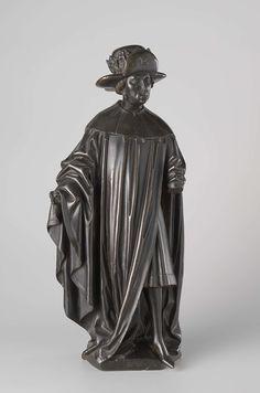 anoniem | Ten weepers from the tomb of Isabella of Bourbon, attributed to Renier van Thienen, c. 1475 - c. 1476 | Hij heeft het linkerbeen naar voren geplaatst en houdt de rechterarm schuin van zich af. Over een kort, tot even over de knieën reikend, onderaan met een bontrand afgezet gewaad met mouwen, draagt hij een op de linkerschouder sluitende mantel met hermelijnen kraag van het Gulden Vlies. Op de bonthoed een kroon en tegen de opgeslagen klep een kleinood; hij draagt hozen.