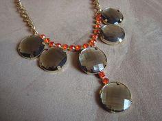 Maxi colar em metal dourado com aplicação de strass laranja e chatons em resina acrílica fumê R$110,00