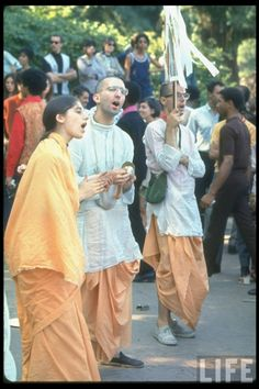 Members of the Hare Krishna sect wearing traditional saffron robes and chanting while walking through a New York City park,