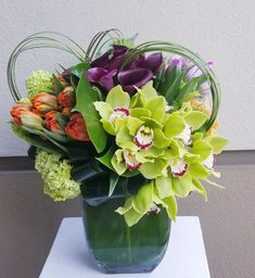 low colorful exotic arrangement composed of plum mini callas, tulips and cymbidium # birthday flower delivery Selena by Apropos Floral & Event Design Tropical Flower Arrangements, Orchid Arrangements, Beautiful Flower Arrangements, Beautiful Flowers, Home Flowers, Exotic Flowers, Flowers Garden, Outdoor Flowers, Tropical Flowers