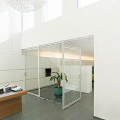 Moderne glazen pivoterende deur met helder glas in een geanodiseerd aluminium frame. Het frame rondom het glas zorgt voor een goede afsluiting. De pivotscharnieren zitten in de deur ingebouwd en er dient niets in de vloer voorzien te worden! Kan dus zowel in nieuwbouw als renovatie toegepast worden.