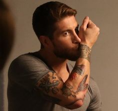 Sergio Ramos' arm tattoos: you can see many modern symbols like feathers and a dream catcher and classic ones like a cross. The tattoo he is kissing on this photo is a wrist band tattoo matching with the one his brother René got.