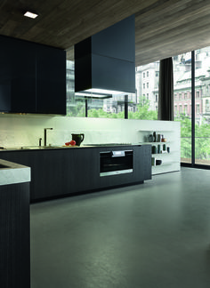 """Varenna_PHOENIX_Kitchen Phoenix with base units in black elm, worktop in mat white Carrara marble thickness 3 1/4"""" and in scotch brite steel thickness 1/4"""", with personalised hob Varenna by Scholtès. Wall panels in DuPont Corian® pearl gray with insert in mat white Carrara marble and steel shelves thickness 1/8"""". Grafite glossy lacquered wall units. Island-hood Glass in black frosted glass."""