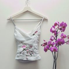 Wowza 🌸🌷🌺 this is a stunner of a little baby doll strappy top | lovely pretty contrasting pink flower design on an innocent white backdrop | open back and flattering ruffle style | slightly cropped | pair with low ride flares and look ultimate 90s | size 8 | ✨Price includes postage ✨