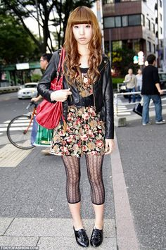 This pretty Japanese girl was photographed on the street in Shibuya. She is wearing a black leather jacket over a flower pattern dress which is belted with a wide belt, lace stockings, and shiny black shoes. She is also carrying a red leather handbag and her hair has a red tint to it as well.