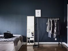 Bedroom and open clothes rail with dark grey accent wall in a fab Swedish small space with different 'zones'. Entrance.