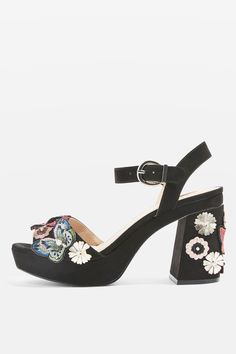 Add height and character to your outfit with these embellished platform sandals. Featuring a tall block heel and adjustable ankle strap, these striking black sandals are dotted with inspiring flora and fauna appliques.