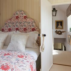 Small guest room with neutral stripe wallpaper and red floral single bed