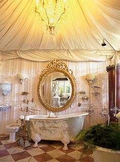 Over-the-top lux bathroom, fabric walls to mimic a tent, antiques & clawfoot / soaking tub.