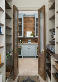 Wood bi-fold pantry doors fitted with rippled glass panels open to a pantry boasting glass front wine coolers positioned beneath a white quartz countertop accenting blue shaker cabinets.