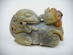 "Carved greenish-grey jade sculpture of a recumbent dragon with its head turned backward, surmounted by a smaller dragon. Smooth surface with incised details carved in bas-relief with russet and brown suffusion, slight calcification and erosion. 2""H x 3"" W"