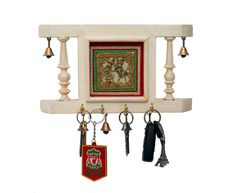 This ethnic key holder is made of wood.It is adorned with Six bells.The dhokra work brass plate is the middle adds sheen to this piece. It can be used as a key ring holder as well as a decoration piece to beautify your house.