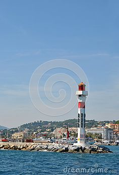 Beautiful lighthouse on the stone pier and cityscape at back, port of Marseille, France