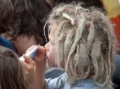young dreadlocked kid watching the Street Entertainers