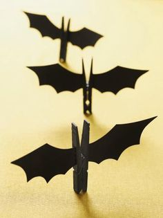 Our easy-to-make bats are defrightful! Paint a wooden clothespin black using acrylic paint. While it's drying, go to familyfunmag. com/printables, download our wing template, and cut it out. Use a pencil to trace two wings onto black card stock. Cut them out. Fold over a tab on the base of each wing where shown and glue them to the sides of the clothespin.