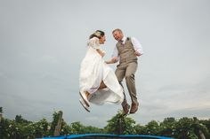 Bride and Groom jumping on a trampoline at Luke & Ariel's Wedding Wedding photos shot by Hitch and Sparrow Wedding Co.
