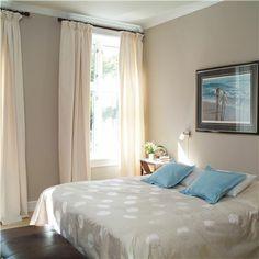 Ihana beigen värinen seinä ja tyylikäs katto sekä pehmeän sävyiset verhot mustalla verhotangolla