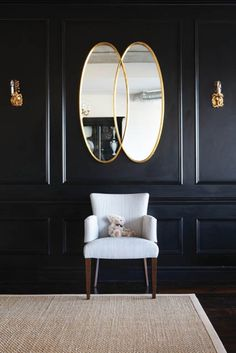 Overlapping Oval Mirror... black wall with gold mirror and sconces, white chair