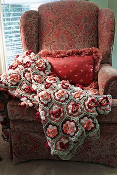 A flowery afghan. and beautiful chair and pillow.