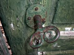 Vieja llave de bronce con ornamentos insertada en su correspondiente cerradura, sobre una puerta de madera muy antigua.