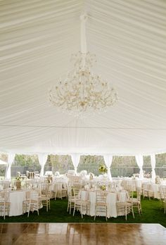 Brides.com: . White is at its best with a draped and pleated tent canopy, sparkling chandelier, and elegant tables, all coming together for a classic look.