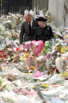 In a file picture taken on September 5, 1997 Britain's Queen Elizabeth II  and Prince Philip, Duke of Edinburgh  view the sea of floral tributes to Diana, the late Princess of Wales, at Buckingham Palace upon their arrival in London.